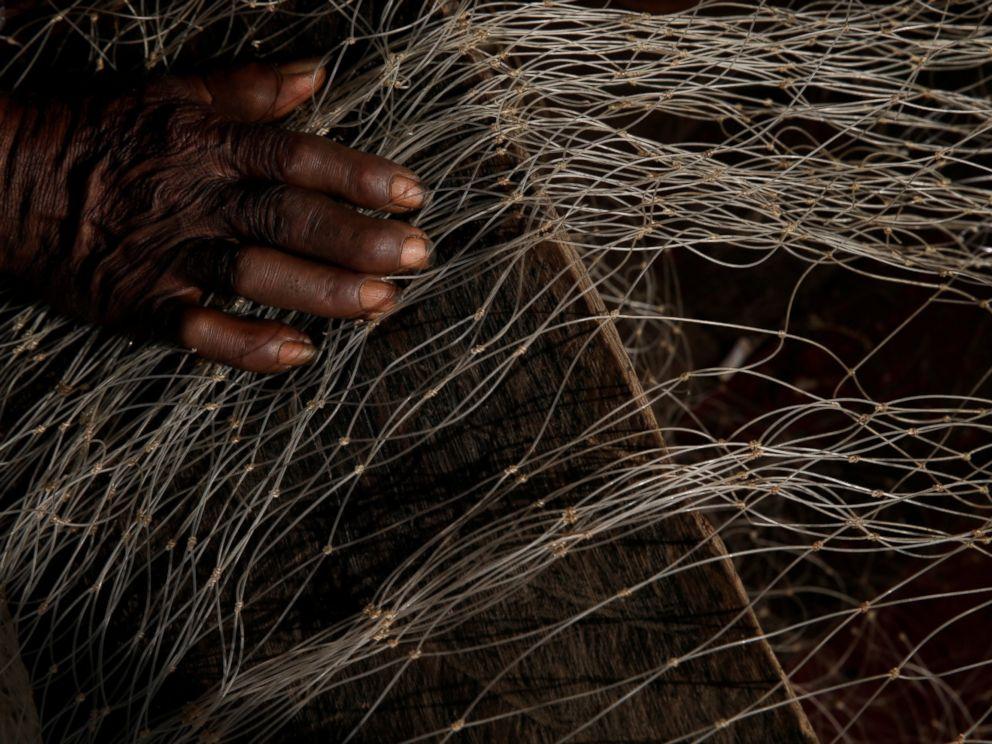 PHOTO: Rodolfo Antonio Ferreira da Silva, 62, works on his fishing net on the banks of the Oiapoque river in Oiapoque city, northern Brazil, April 2, 2017.