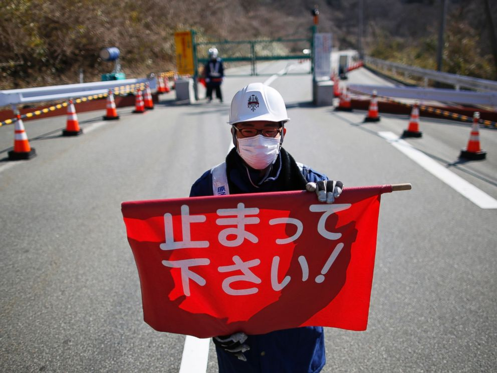 PHOTO: A security guard holds a flag, which reads Please Stop!, as he stand by a steel gate at the border near Fukushima