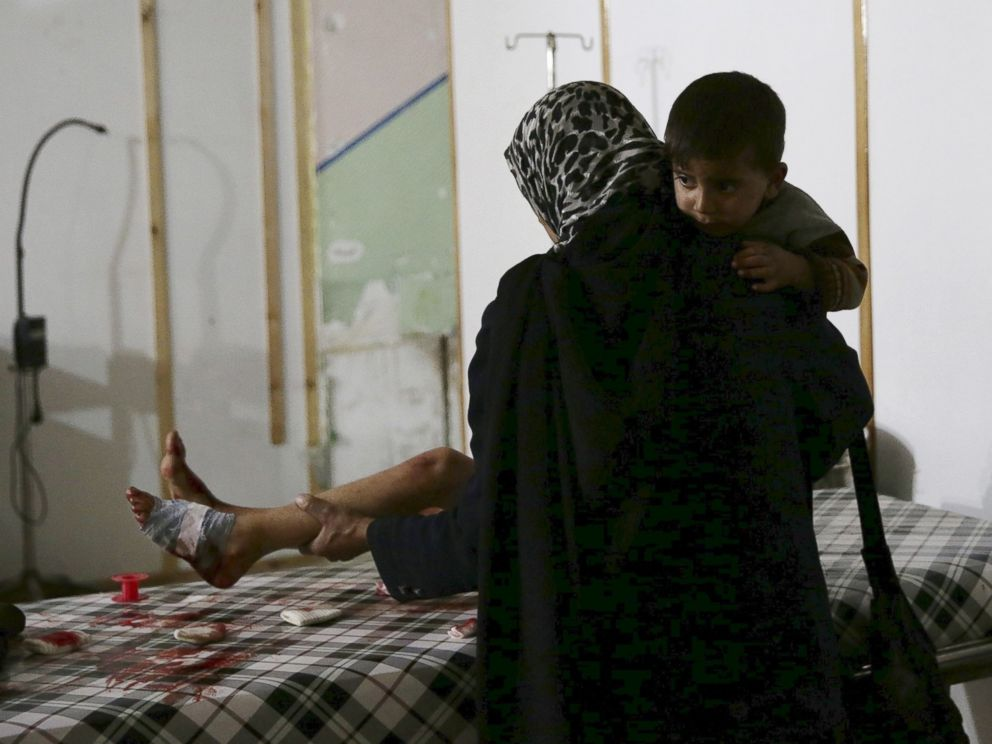 PHOTO: A woman carries a son while tending to the wounds of another son inside a field hospital in the Douma neighborhood of Eastern Ghouta, Syria, Nov. 19, 2015.