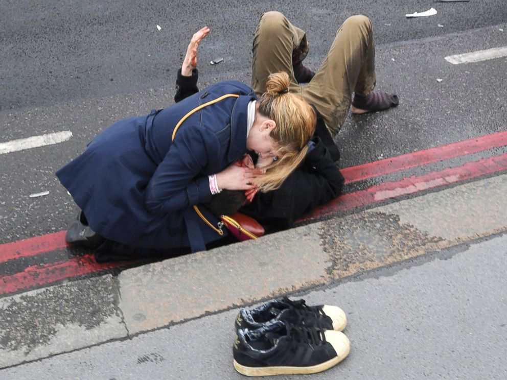 PHOTO: A woman assists an injured person after an incident on Westminster Bridge in London, March 22, 2017.