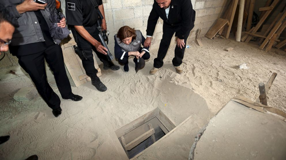 """Mexico's Attorney General Arely Gomez Gonzalez looks into the entrance of a tunnel connected to the Altiplano Federal Penitentiary that was used by drug lord Joaquin """"El Chapo"""" Guzman to escape on the outskirts of Mexico City, July 12, 2015."""