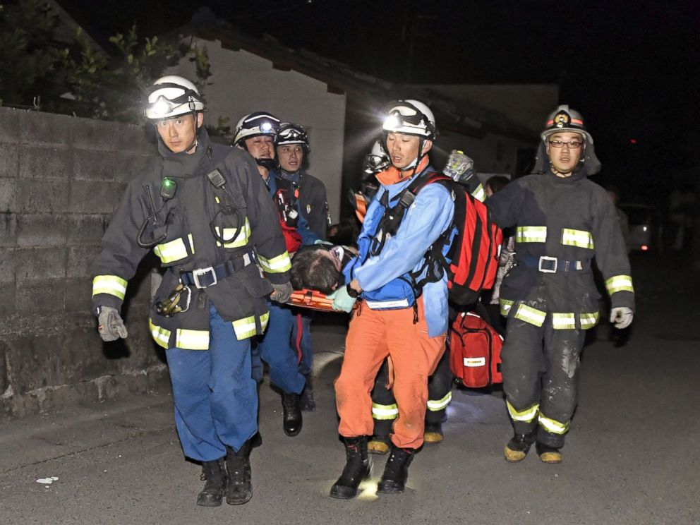 PHOTO: Rescue workers use a stretcher to carry a man who was rescued from a collapsed house in Mashiki town, Kumamoto prefecture, southern Japan, April 15, 2016.
