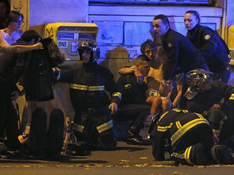 PHOTO: French fire brigade members aid an injured individual near the Bataclan concert hall following fatal shootings in Paris, Nov. 13, 2015.