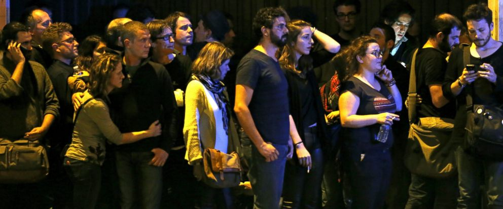 PHOTO: People react as they gather to watch the scene near the Bataclan concert hall following fatal shootings in Paris, France, Nov. 13, 2015.