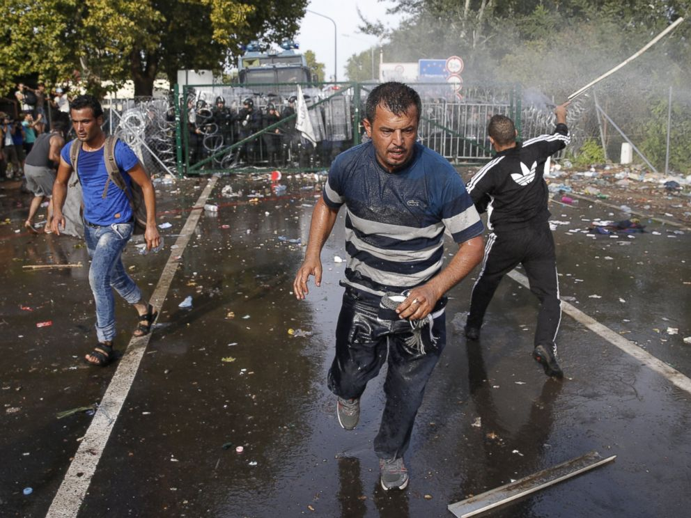 PHOTO: Migrants run as Hungarian riot police fires tear gas and water cannon at the border crossing with Serbia in Roszke, Hungary, Sept. 16, 2015.