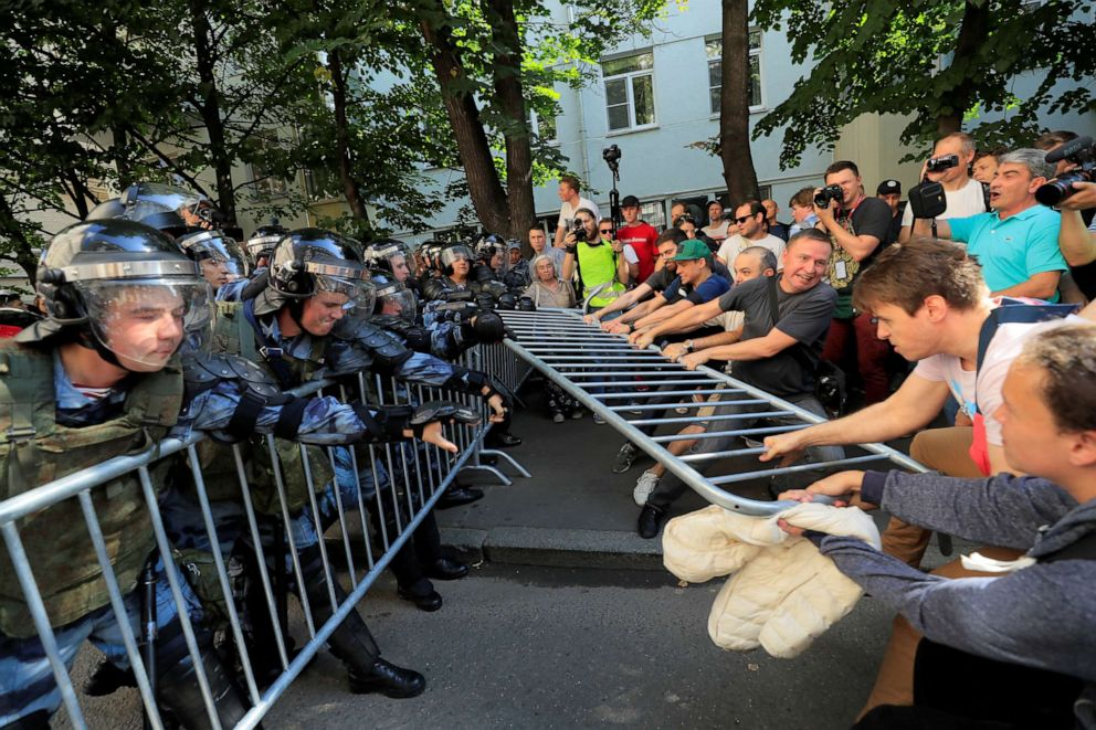 PHOTO:Demonstrators attempt to remove fences during a rally calling for opposition candidates to be registered for elections to Moscow City Duma, the capitals regional parliament, in Moscow, July 27, 2019.