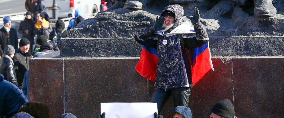 PHOTO: A demonstrator with a Russian national flag wrapped in his shoulders shouts slogans during a rally in Vladivostok, Russia, Jan. 28, 2018.
