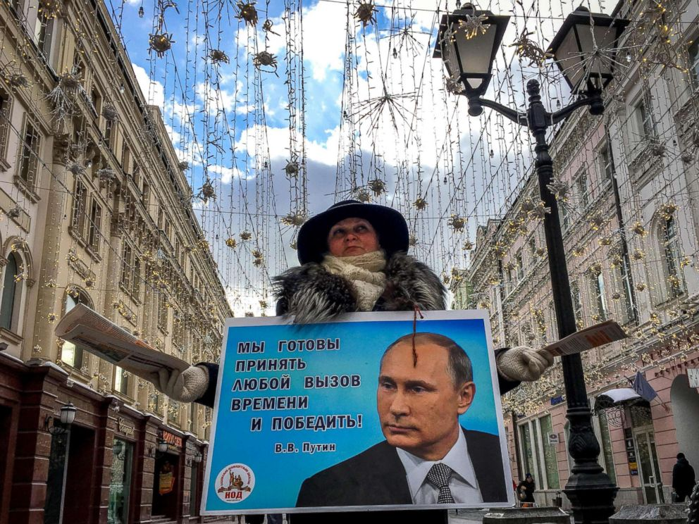 PHOTO: An activist distributes election leaflets in support of presidential candidate, President Vladimir Putin on a street in downtown Moscow, March 16, 2018.