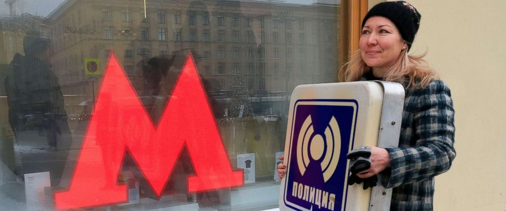 "PHOTO: A woman leaves a gift shop after purchasing a retro signboard that reads, ""Police,"" in Moscow, Dec. 25, 2018."