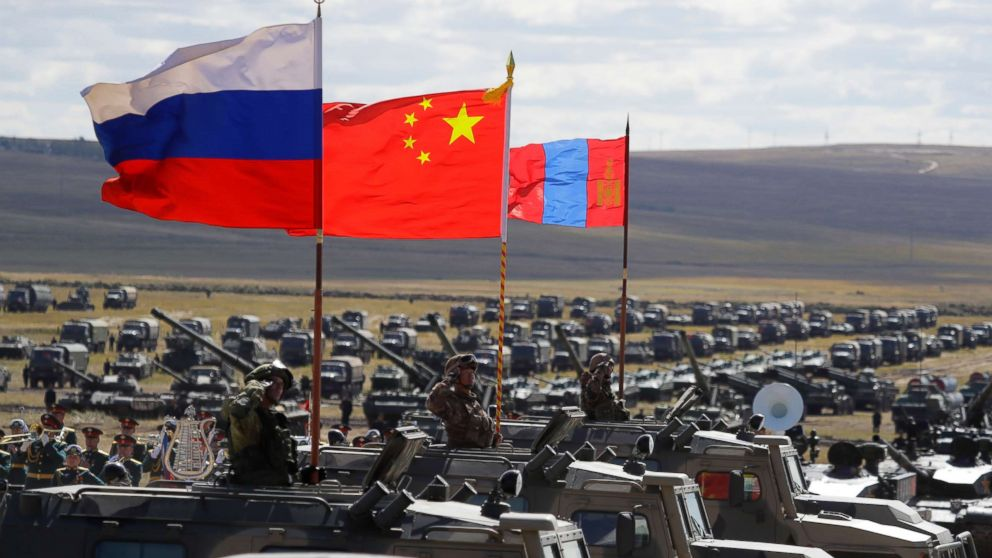 Russian, Chinese and Mongolian national flags set atop armored vehicles during military exercises in Eastern Siberia, Russia, Sept. 13, 2018.