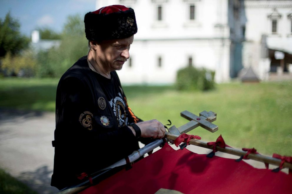 PHOTO: Valeriy, a member of the Union of Orthodox Banner-Bearers, prepares a banner for a morning procession to commemorate 100 years since the killing of Tsar Nicholas II, in Spaso-Andronikov Monastery, in Moscow, July 17, 2018.