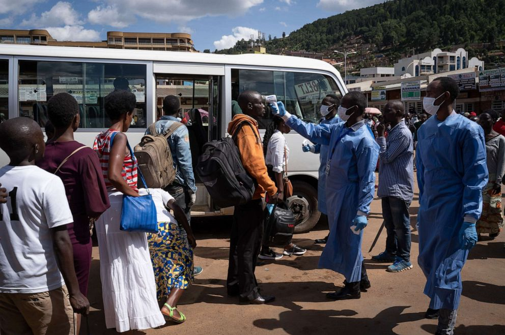In this March 22, 2020, file photo, a staff member of the Rwanda Biomedical Center (RBC) screens passengers at a bus station after the government suspended all unnecessary movements for two weeks to curb the spread of COVID-19 in Kigali, Rwanda.Simon Wohlfahrt/AFP via Getty Images, FILE