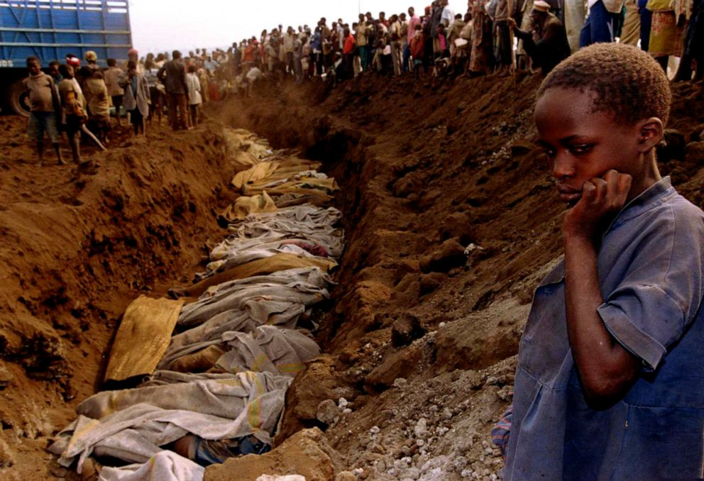 PHOTO: A Rwandan refugee girl stares at a mass grave where dozens of bodies have been laid to rest, July 20, 1994.