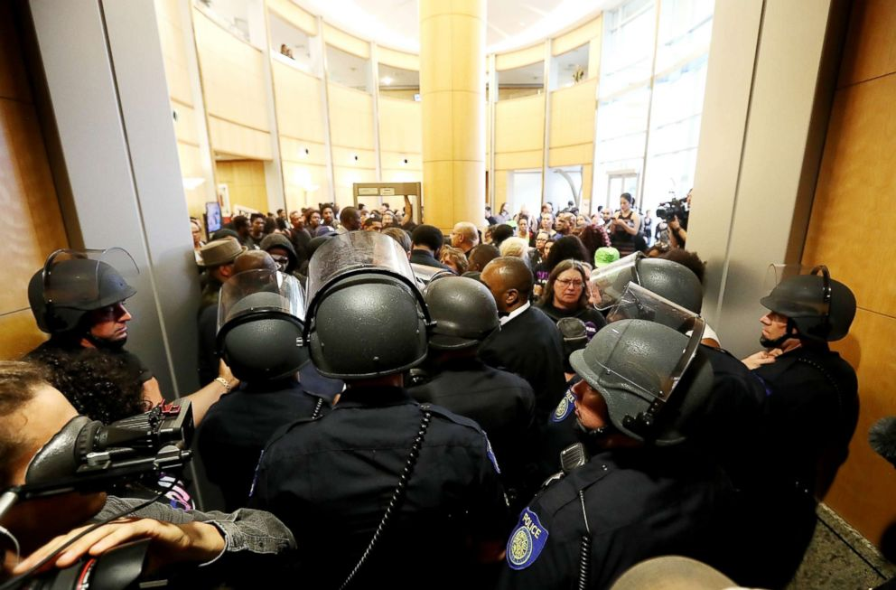 PHOTO: Sacramento police officers in riot gear block the entrance to a city council meeting at Sacramento City Hall on March 27, 2018, in Sacramento, Calif.