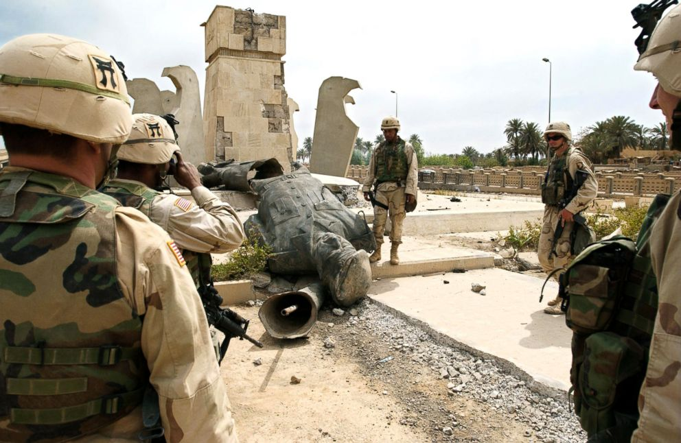 PHOTO: US soldiers shoot a picture in front of the toppled statue of Iraqi leader Saddam Hussein, April 13, 2003, in Baghdad.