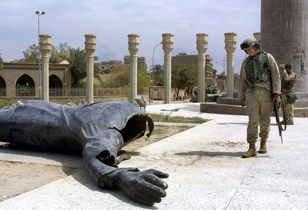 PHOTO: US Marines walk pass a dismounted statue of Saddam Hussein on Baghdads al-Fardous square, April 10, 2003.