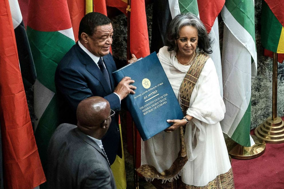 President Sahle Work Zewde right recieves a book of the Constitution from former President Mulatu Teshomea at the Parliament in Addis Ababa Oct. 25 2018
