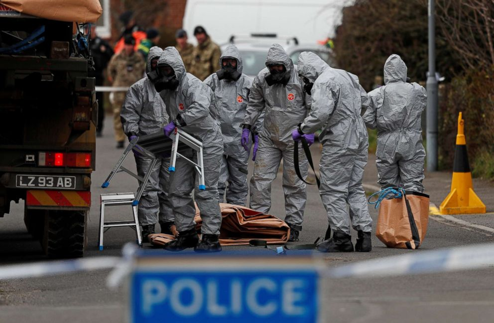 PHOTO: British Military personnel wearing protective coveralls work to remove a vehicle connected to the March 4 nerve agent attack in Salisbury, from a residential street in Gillingham, southeast England on March 14, 2018.