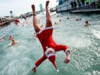 PHOTO: A participant in a Santa Claus costume jumps into the water during the 109th edition of the Copa Nadal (Christmas Cup) swimming competition in Barcelona, Dec. 25, 2018.