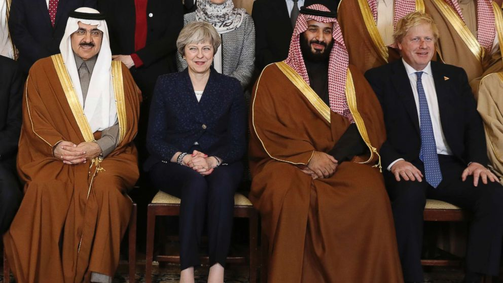 Britain's Prime Minister Theresa May, 2nd left, sits with Saudi Crown Prince Mohammed bin Salman, 2nd right, and other members of the British government and Saudi ministers and delegates inside 10 Downing Street in London, March 7, 2018, for a group photo.