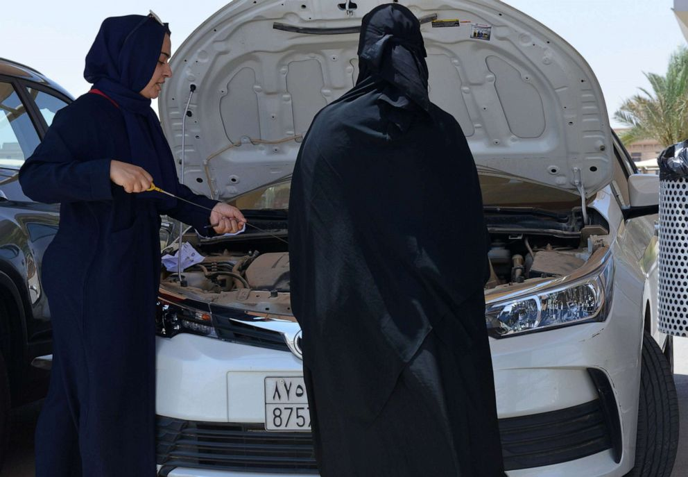 PHOTO: A Saudi trainee shows a female driver how to check a cars engine oil level at the Saudi Driving School (SDS), in Riyadh, Saudi Arabia on June 24, 2019.