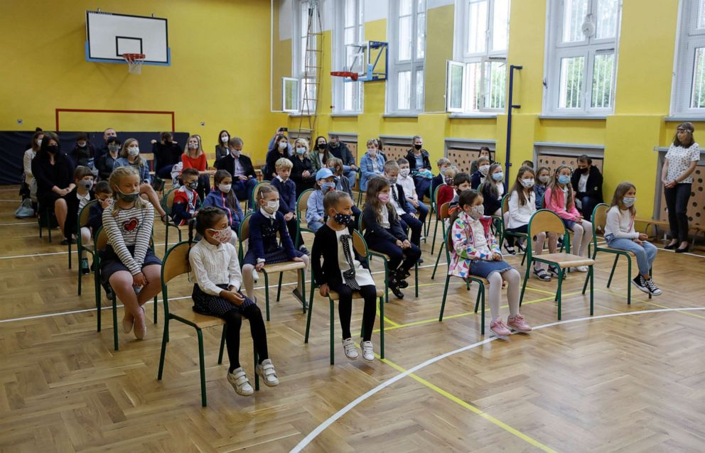 PHOTO: Children wearing face masks listen to the school director's speech during the first day of a new academic year in Warsaw, Poland, on Sept. 1, 2020, amid the coronavirus pandemic.