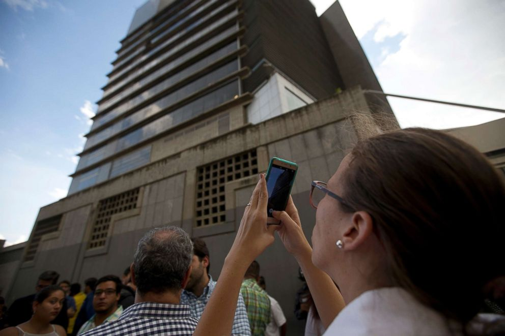 Manuela Bolivar, a lawmaker and member of the First Justice party, takes photos of the Bolivarian National Security Service (SEBIN) headquarters in Caracas, Venezuela, Oct. 8, 2018. Venezuela's Attorney General Tarek William Saab said that councilman Fernando Alberto Alban Salazar, who was arrested on suspicion of involvement in a failed assassination attempt on President Nicolas Maduro, committed suicide while jailed at SEBIN.