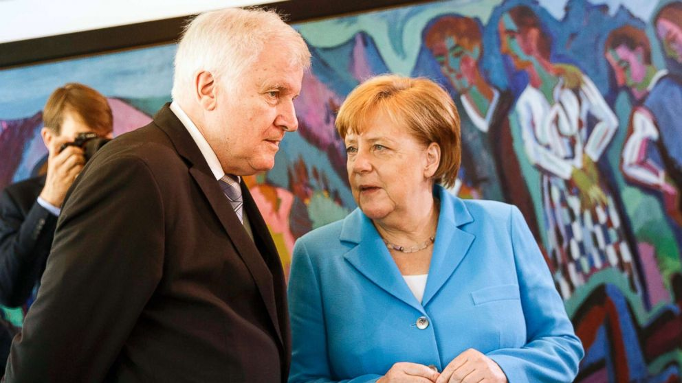 German Chancellor Angela Merkel speaks to German Interior Minister Horst Seehofer after the arrival for the weekly government cabinet meeting, June 13, 2018, in Berlin.