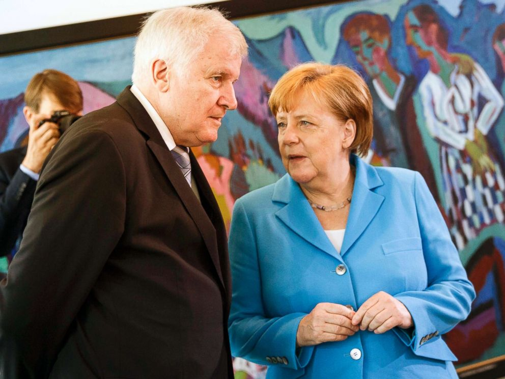 PHOTO: German Chancellor Angela Merkel speaks to German Interior Minister Horst Seehofer after the arrival for the weekly government cabinet meeting, June 13, 2018, in Berlin.