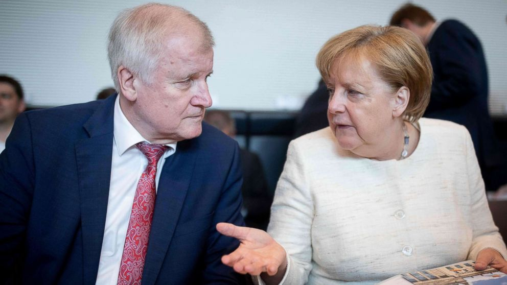 German Chancellor and leader of the Christian Democratic Union (CDU) party Angela Merkel talks with German Interior Minister Horst Seehofer (CSU) prior a parliamentary group meeting CDU/CSU at the Reichstag parliament building, June 12, 2018, in Berlin.