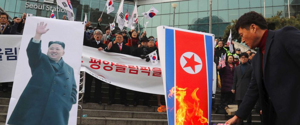 PHOTO: South Korean protesters burn a North Korean flag, right, and a picture ,left, of North Korean leader Kim Jong-Un during an anti-North Korea rally outside Seoul station in Seoul, Jan. 22, 2018, as a North Korean delegation arrives at the station.