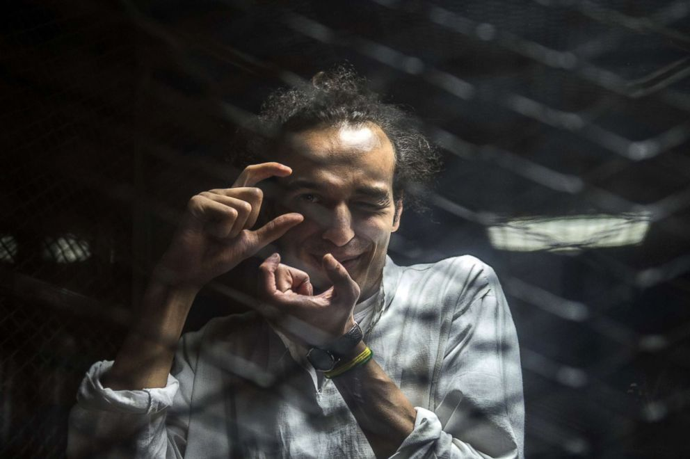 PHOTO: Egyptian photojournalis Mahmoud Abu Zeid, known as Shawkan, mimics taking a photograph from inside a soundproof glass dock during his trial in Cairo, Aug. 9, 2016.