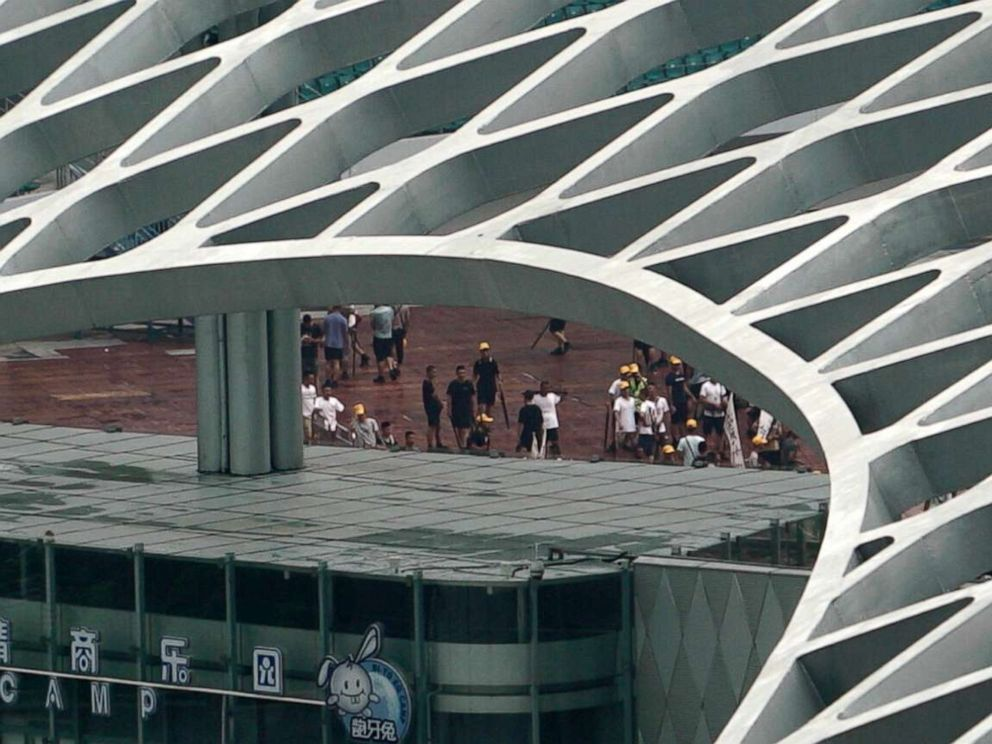 PHOTO: During the daily simulation drills, some members of the Peoples Armed Police were seen role-playing the part of would-be protesters, looking uncannily like the ones in neighboring Hong Kong, complete with yellow headgear.