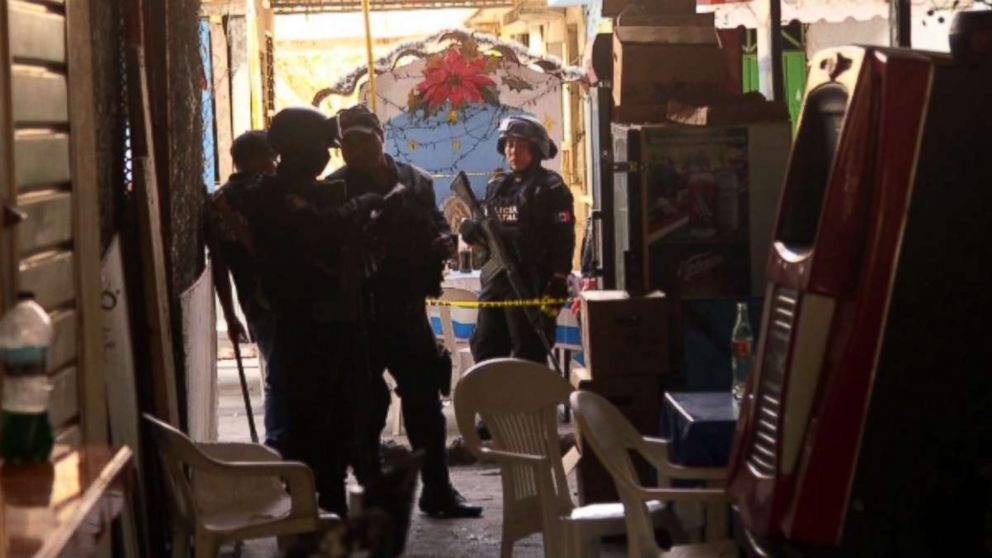 Mexican authorities access a homicide scene in Acapulco where a food stand owner was shot and killed.