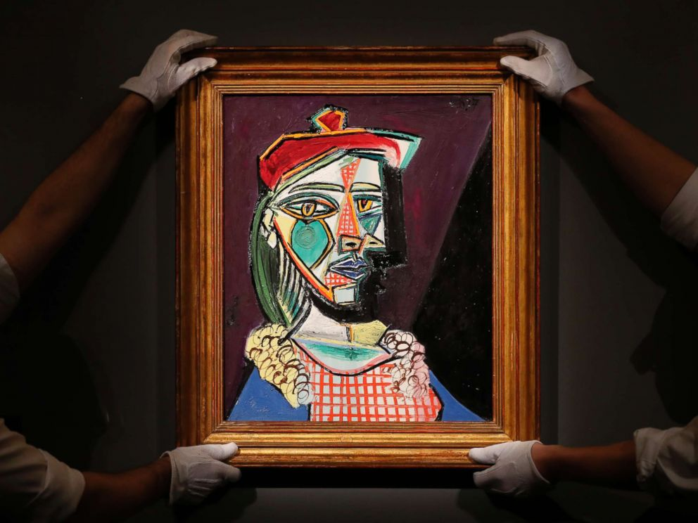 PHOTO: Sothebys employees hold up Pablo Picasso 1937 Femme au beret et a la robe quadrillee, at Sothebys auction house in London, Feb. 22, 2018.