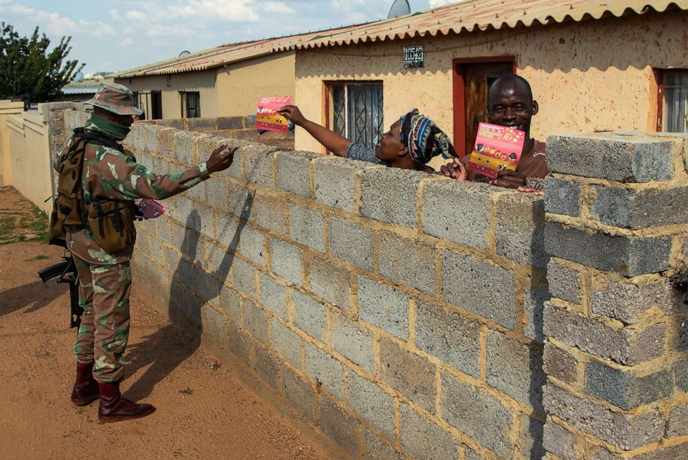 A soldier hands out flyers about the novel coronavirus to a resident on the streets of Soweto, South Africa, April 23, 2020, as the country remains in lockdown for a fourth week in a bid to combat the spread of the coronavirus.Themba Hadebe/AP