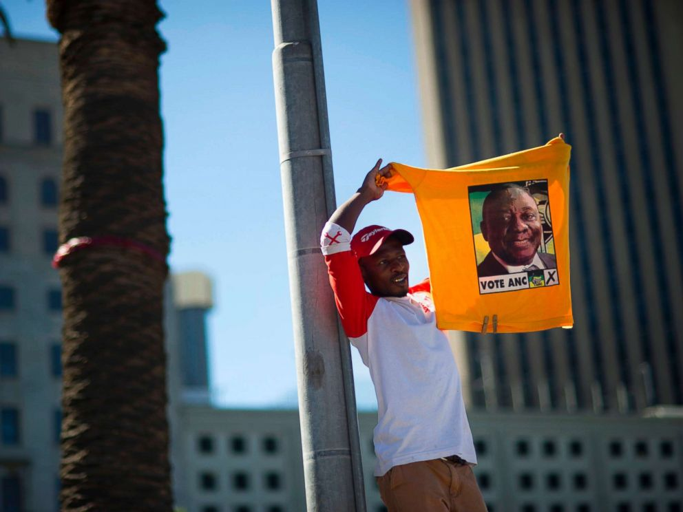 PHOTO: A supporter of South Africas ruling African National Congress holds up a shirt featuring newly-elected ANC president and South African Deputy President, Cyril Ramaphosa, during a rally on Feb. 11, 2018 in Cape Town.