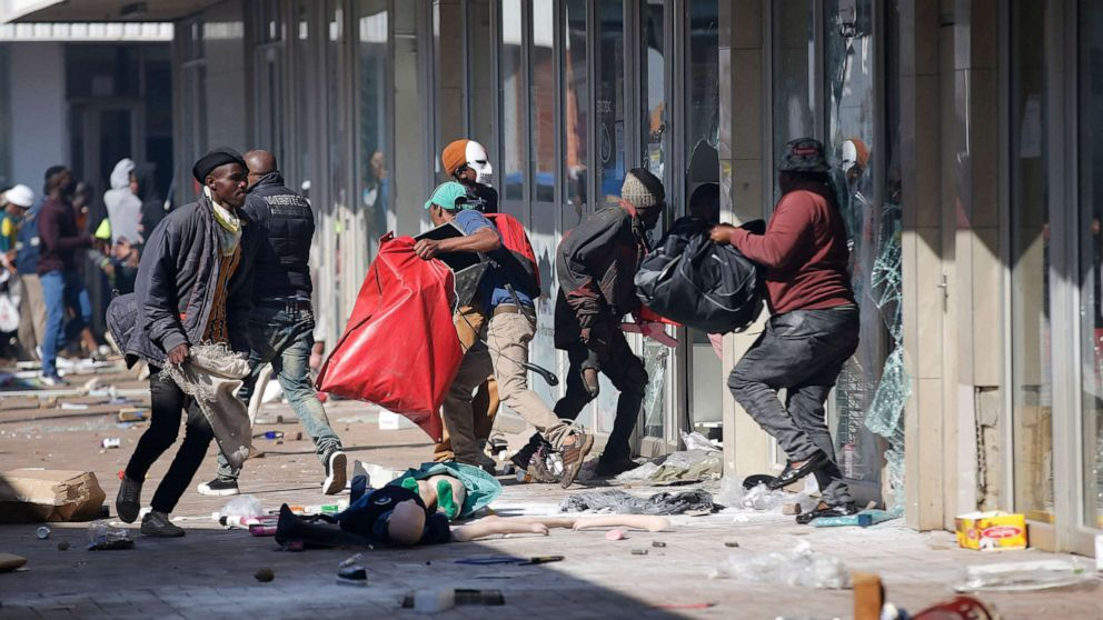 PHOTO: People carry goods as they loot and vandalize the Lotsoho Mall in Katlehong township, east of Johannesburg, on July 12, 2021.