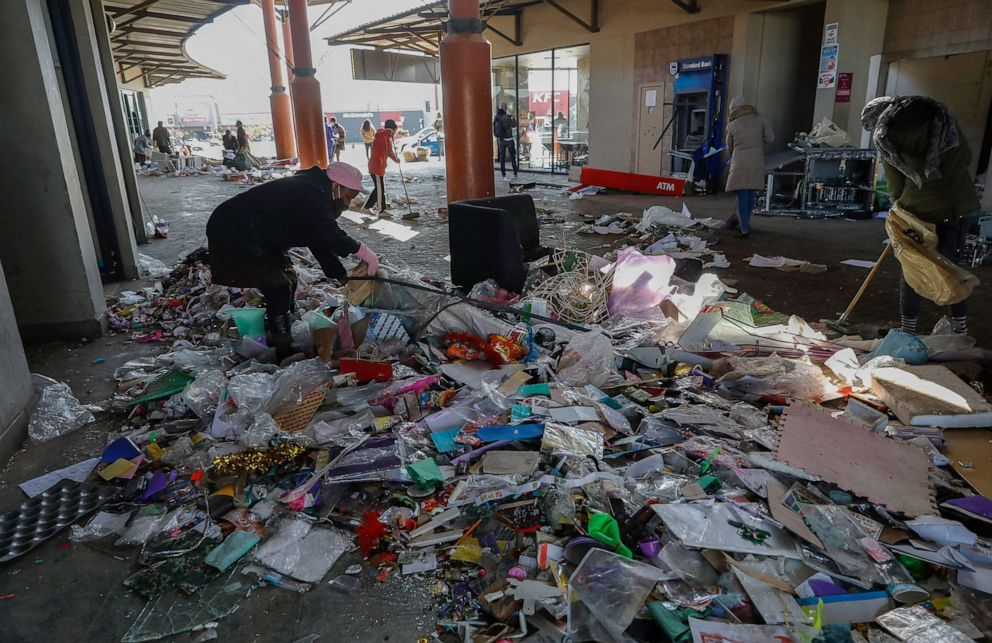 PHOTO: Locals use brooms while volunteering to clean the Diepkloof Square following looting and vandalism in Soweto, Johannesburg on July 14, 2021.