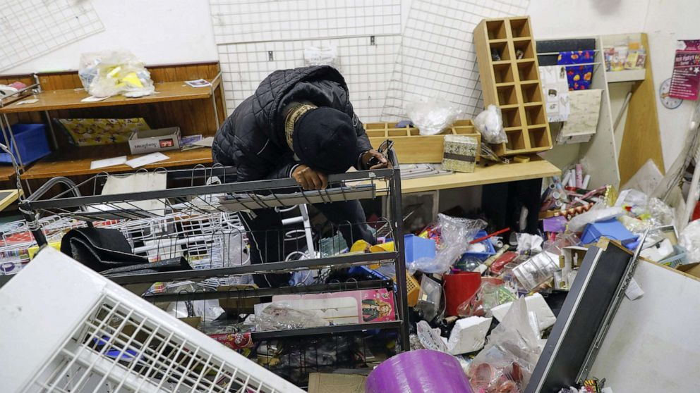 PHOTO: Thandi Johnson, a shop owner, weeps inside her looted store at the Diepkloof Square area in Soweto, Johannesburg on July 13, 2021.