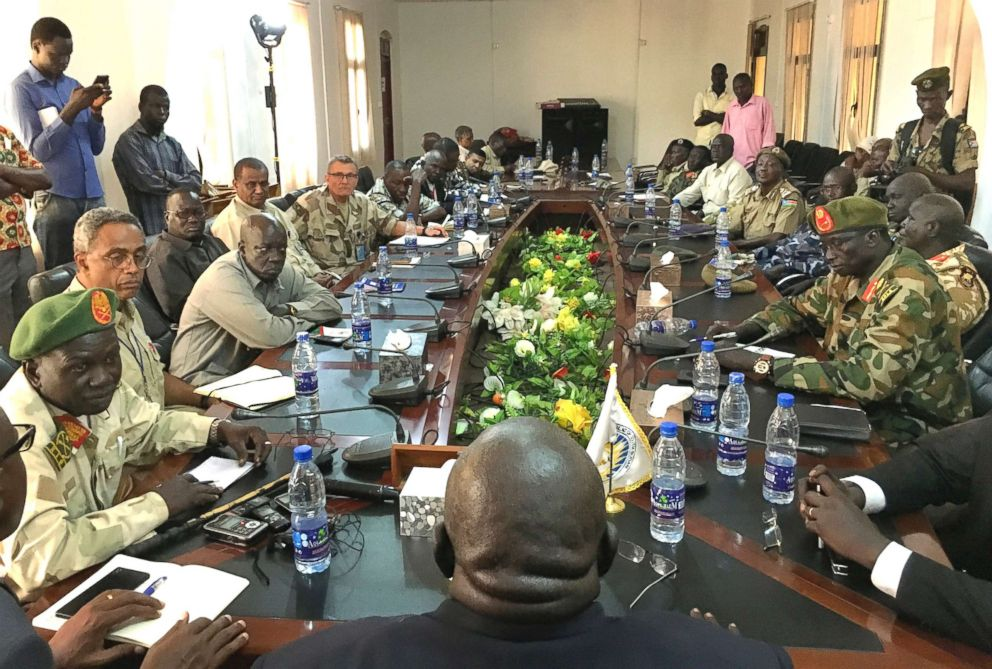 PHOTO: In this photo taken Thursday, Nov. 22, 2018, a South Sudan armed opposition commander Ashab Khamis, far-left, and a government army Gen. Keer Kiir Keer, far-right, attend high level talks in Wau, South Sudan.