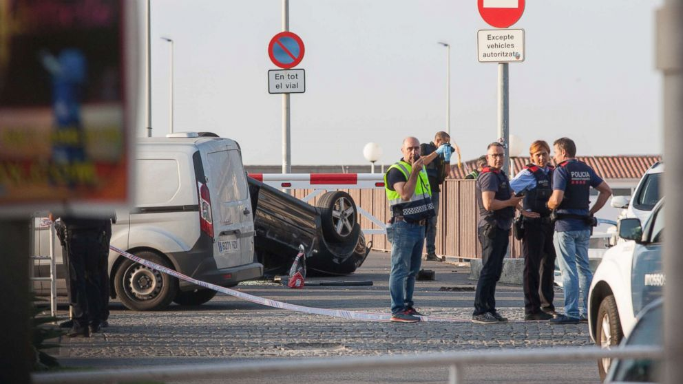 Police officers speaking next to a rolled over car at the location where police shot dead five terrorists in Cambrils, Spain, Aug. 18, 2017.