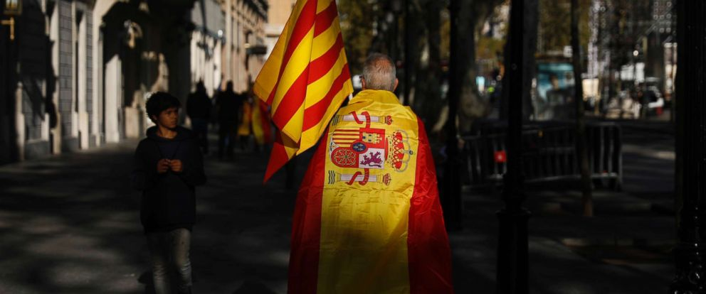 PHOTO: A man wearing a Spanish flag walks along a street ahead of a rally against Catalonias declaration of independence, in Barcelona, Spain, Oct. 29, 2017.
