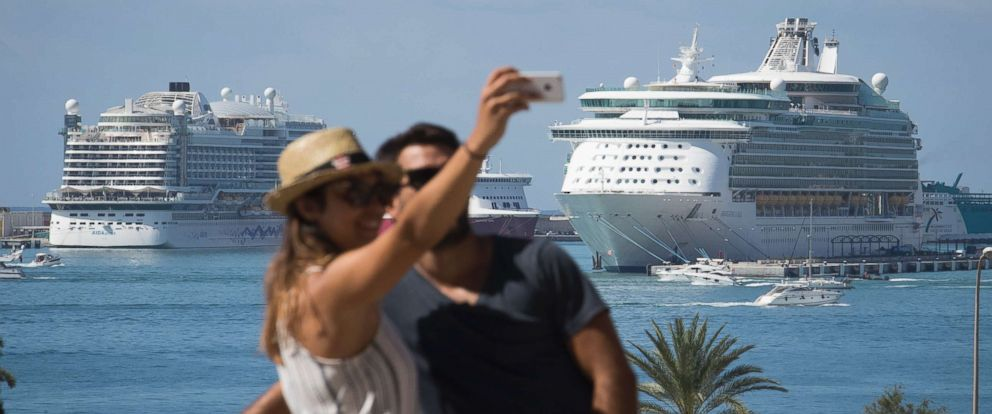 PHOTO: A couple takes a selfie photo with some docked cruise ships in the background, in Palma de Mallorca on Aug. 12, 2017.