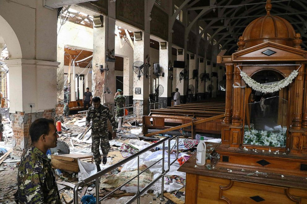 PHOTO: Sri Lankan security guard walks past corpses covered with blankets in the midst of rubble at St. Anthony's Shrine after an explosion at the Church of Kochchikade in Colombo, April 21, 2019.
