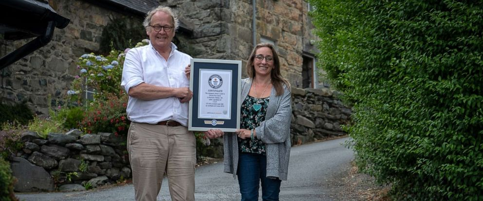 PHOTO: Gwyn Headley and Sarah Badhan, stand on Ffordd Pen Llech with a certificate from Guinness World Records, confirming that the road is the steepest street in the world, in the seaside town of Harlech, North Wales.
