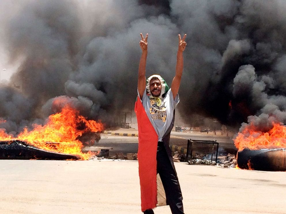 PHOTO: In this June 3, 2019, file photo, a protester flashes the victory sign in front of burning tires and debris near Khartoums army headquarters, in Khartoum, Sudan.