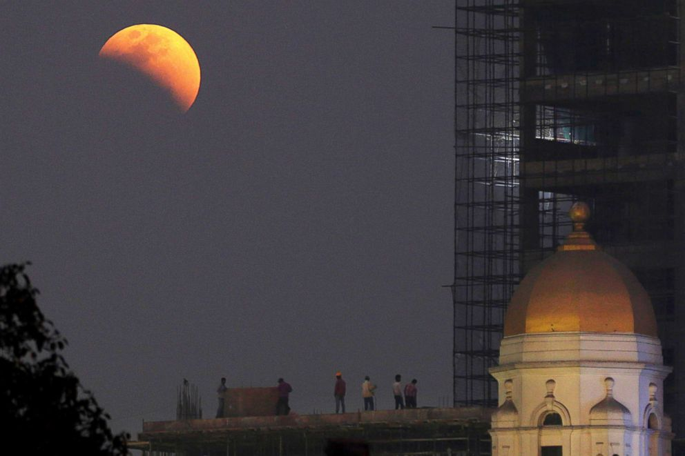 PHOTO: People watch the super moon and full eclipse develop near a heritage building in Calcutta, Eastern India, Jan. 31, 2018.