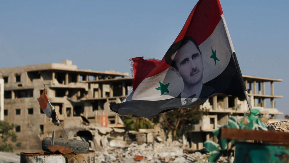 A Syrian national flag with the picture of the Syrian President Bashar Assad hangs at an Army check point, in the town of Douma in the eastern Ghouta region, Syria, July 15, 2018.