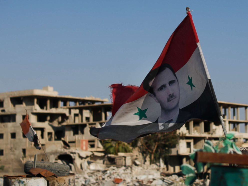 PHOTO: A Syrian national flag with the picture of the Syrian President Bashar Assad hangs at an Army check point, in the town of Douma in the eastern Ghouta region, Syria, July 15, 2018.